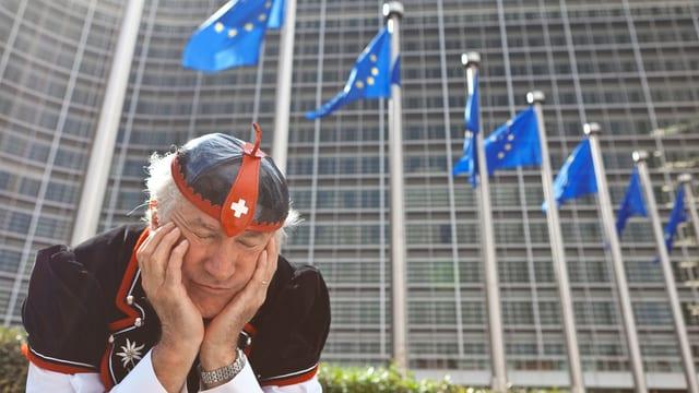 Symbolbild: Ein Mann in Schweizer Tracht sitzt vor dem Gebäude der EU-Kommission in Brüssel, hat das Kinn in die Hände gestützt und scheint zu schlafen.