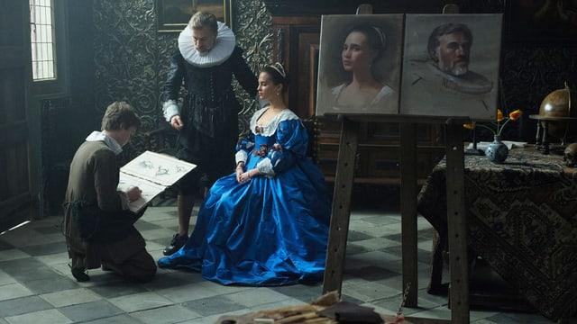 Ein Maler kniet vor einem Ehepaar, er hat ein Blatt Papier auf dem Knie und malt. Der Ehemann steht, die Ehefrau sitzt auf einem Stuhl.