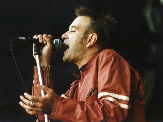 Ein Mann in roter Lederjacke singt.