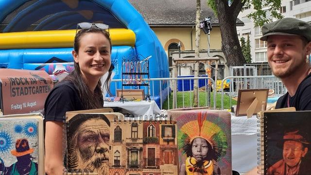 Maryon e Giancarlo Capararo vendan lur cudischs creai sez en il parc da la citad.