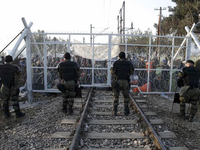 Polizisten in Kampfmontur stehen vor einem Gittertor, das ein Bahngeleise geschlossen hält, dahinter viele Menschen.