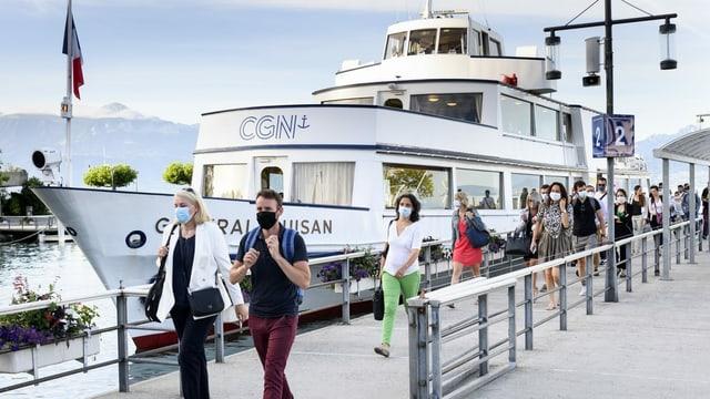 Menschen laufen auf dem Steg weg von einem Schiff. Alle tragen eine Maske über Nase, Mund und Kinn.