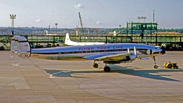 Ein Flugzeug der Linie Flying Tiger steht auf einem Rollfeld.