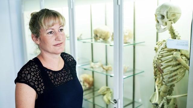 Eine Frau steht vor einer Vitrine mit Skeletten und Knochen.
