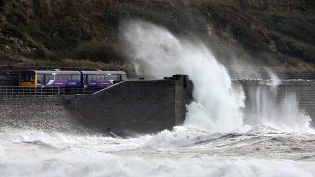 Ein Zug fährt entlang der englischen Küste und wird von einer hohen Welle getroffen