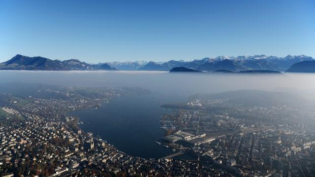Blick aus der Luft auf die Stadt Luzern. Über der Dunstschicht das Alpenpanorama und blauer Himmel.
