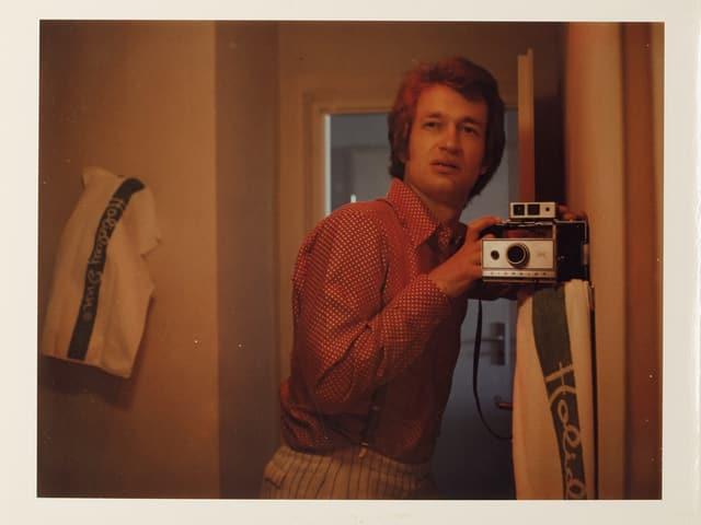Ein junger Mann fotografiert sich selbst.