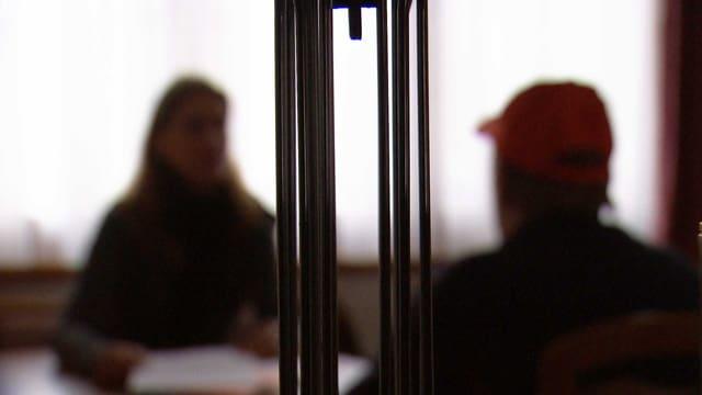 Zwei Silhouetten von Personen, die sich gegenüber sitzen und miteinander sprechen.