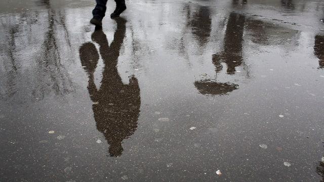 Fussgänger spiegeln sich im regennassen Asphalt.