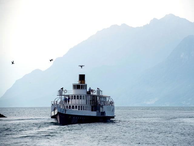 Ein Dampfschiff fährt in der Abenddämmerung über einen See.