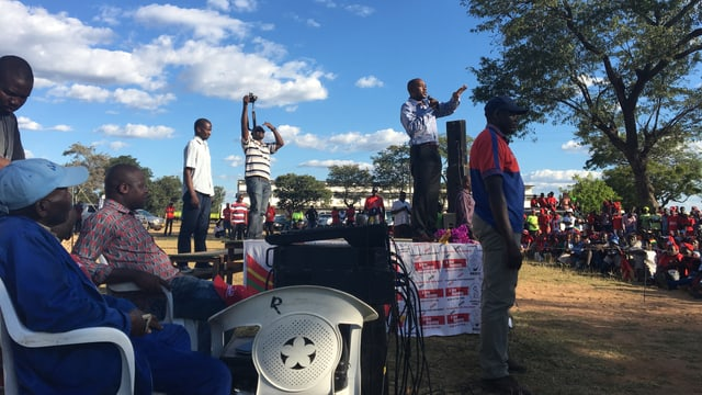 Mann auf Podest spricht in ein Mikrofon unter freiem Himmel.
