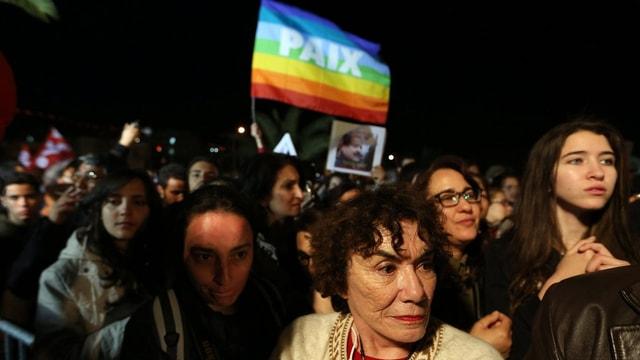 Eine Friedensfahne über Teilnehmern einer Demonstration