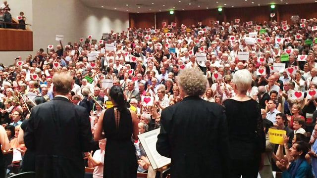 Blick von der Orchesterbühne ins Publikum, dass eine Standingovation gibt und Herzchen auf Plakaten in die Höhe halten.
