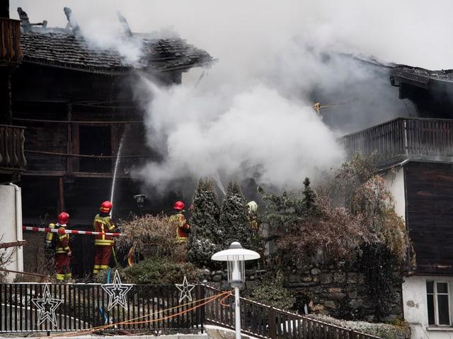 Feuerwehrmänner löschen Gebäude in Brand.