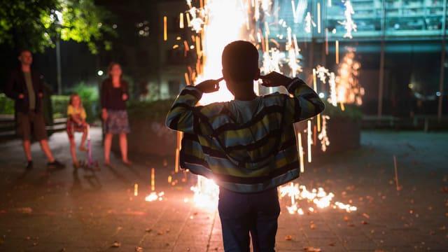 Ein Kind schaut auf einen Feuerwerksvulkan