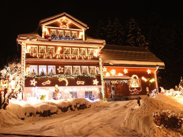Beleuchtetes Weihnachtshaus in der Nacht.