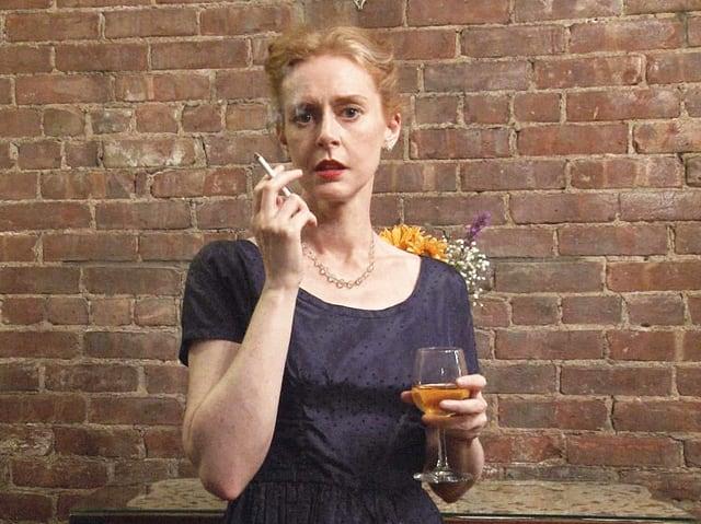 Eine Frau mit rotem, zusammengebundenem Haar. Sie trägt ein Weinglas und raucht.