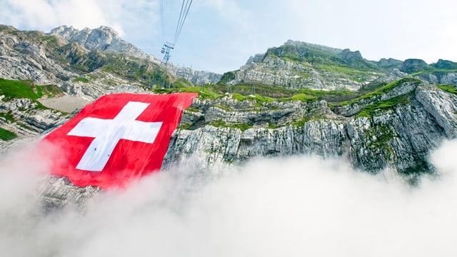 Eine Schweizer Flagge an einem Steilhang.