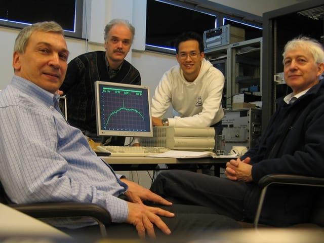 Vier Männer sitzen um einen Computer, auf dessen Bildschirm die grafische Darstellung eines Signals zu sehen ist.