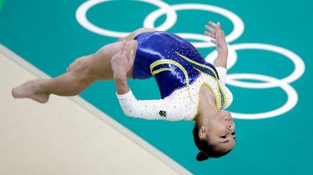 Eine Turnerin fliegt über das Olympische Logo.