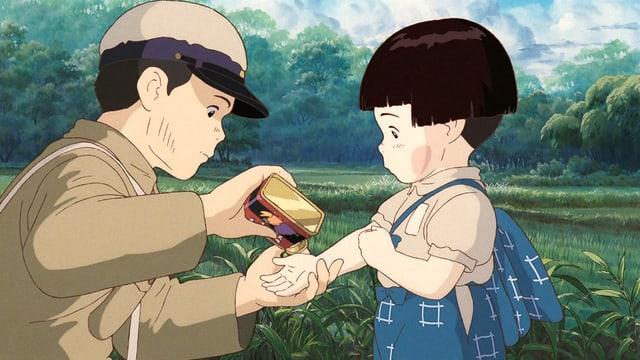 Ein junge gibt seiner kleinen Schwester ein Bonbon auf die Hand.