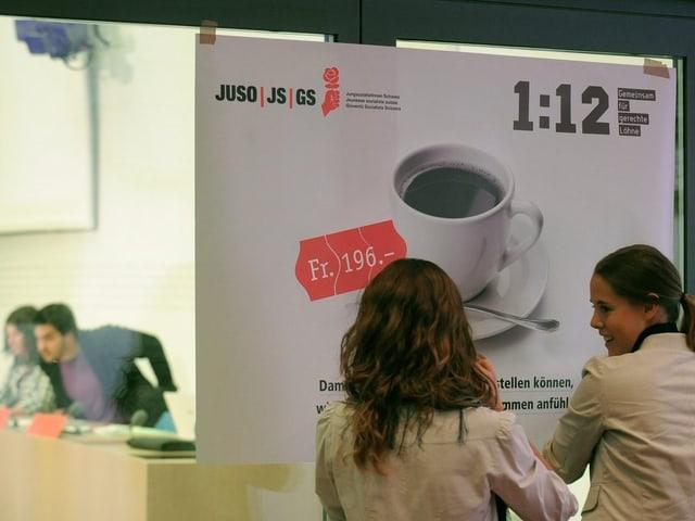 Zwei Frauen betrachten das Abstimmungsplakat zur «1:12»-Initiative.