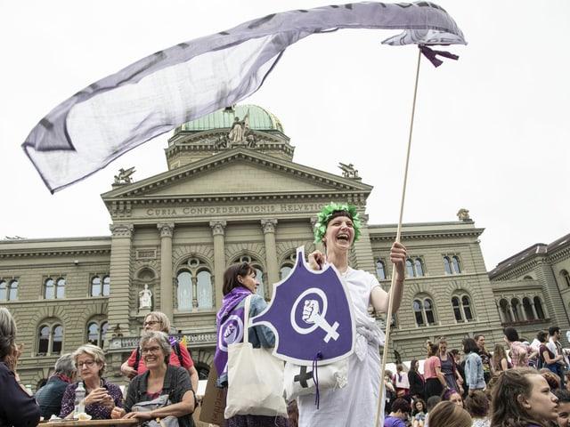 Eien Frau in Helvetiakostüm, mit Frauenstreik-Banner, steht lachend vor dem Bundeshaus.