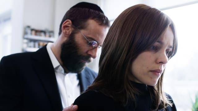 Jüdischer Mann steht hinter jüdischer Frau.