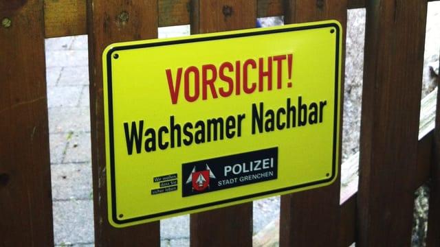 """Ein gelbes Schild, auf dem mit roter Schrift steht """"Vorsicht"""" und mit schwarzer Schrift """"Wachsamer Nachbar"""", hinzu kommt das Logo der Grenchner Stadtpolizei."""