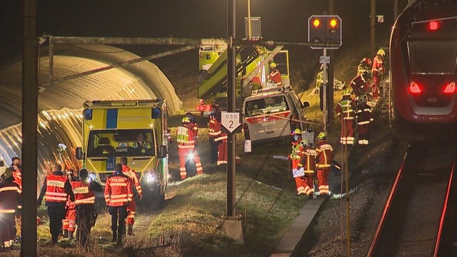 Zahlreiche Rettungskräfte neben einem Zug