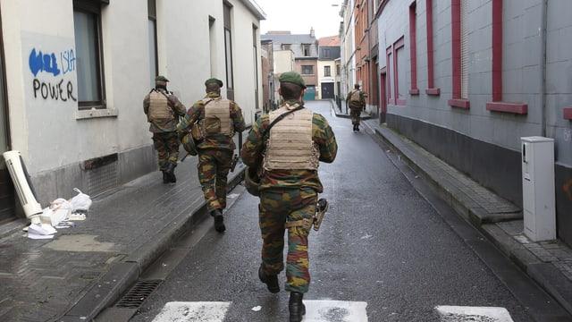 Vier Polizisten durchkämmen eine Strasse in Molenbeek, Grafitti links an der Wand.