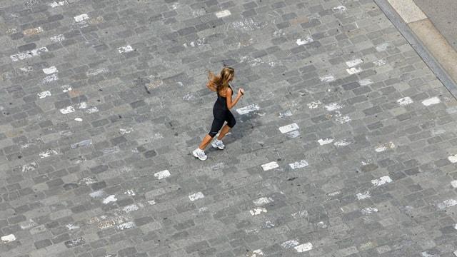 Aufnahme aus Vogelperspektive: Eine Joggerin läuft über Pflastersteine.