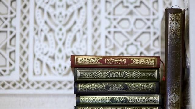 Ausgaben des Korans auf einer Beige.