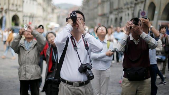 Touristen fotografieren den Zytglogge-Turm in Bern.