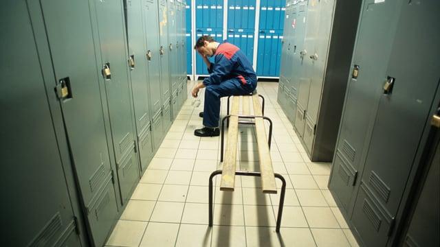 Verzweifelter Mann in Overall sitzt in einer leeren Garderobe