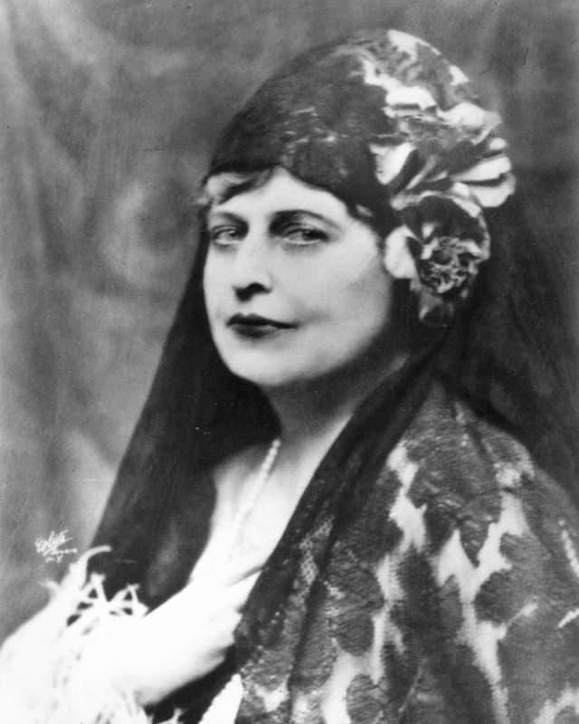 Eine Frau mit Kopfbedeckung schaut in die Kamera.