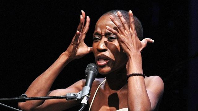 Eine Frau singt, mit Geste und Gesichtsausdruck, der sowohl Wut als auch Verzweiflung andeutet.