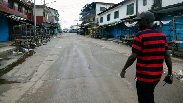 Ein Mann geht durch eine ausgestorbene Strasse.