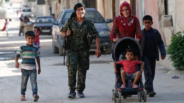 Eine junge Frau in Uniform und mit Gewehr begleitet eine Frau, die einen Kinderwagen schiebt und von zwei Buben begleitet wird.
