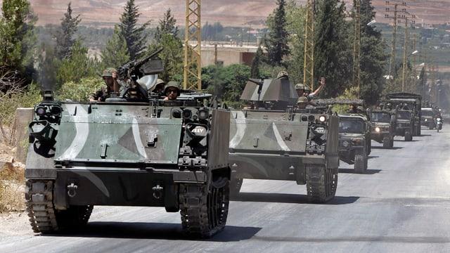 Kolonne aus gepanzerten Armeefahrzeugen mit Soldaten fahren auf einer Strasse.