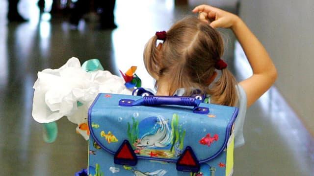 Schulmädchen mit Rucksack von hinten kratzt sich am Kopf