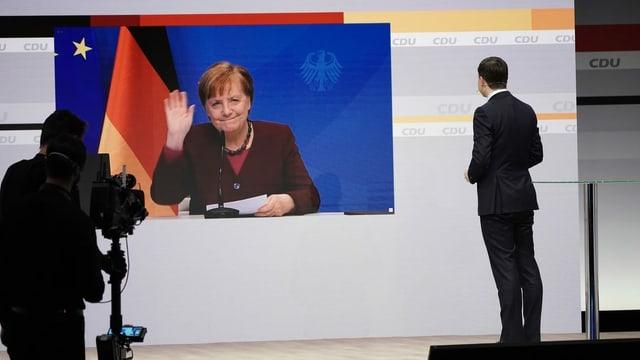 Merkel grüssend auf einer Videowand