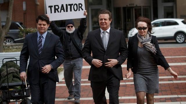 Ehepaar auf dem Weg zum Gericht, im Hintergrund ein Protester.