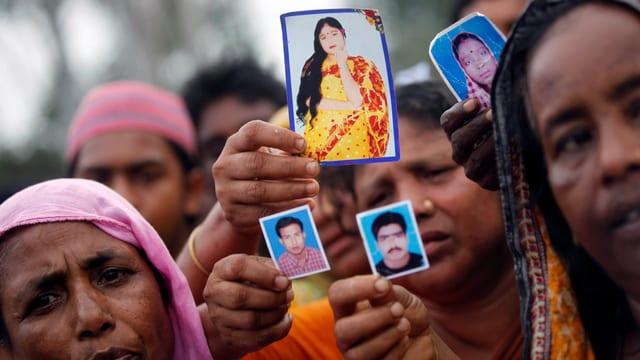 Verwandte zeigen Fotos von Opfern der Katastrophe in Bangladesh.
