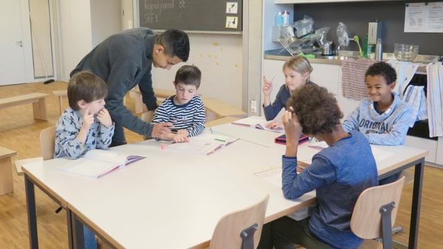 Grosser Schüler und fünf Kinder an einem Tisch in einem Schulzimmer