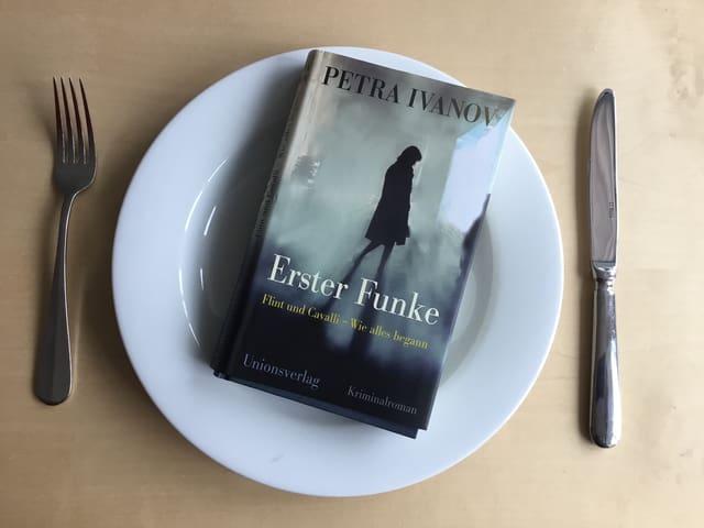 Das Buch «Erster Funke» von Petra Ivanov auf weissem Teller serviert mit Besteck