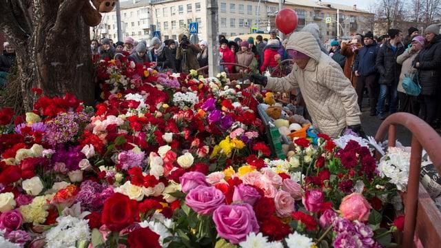 Menschen legen Blumen für die Opfer nieder.