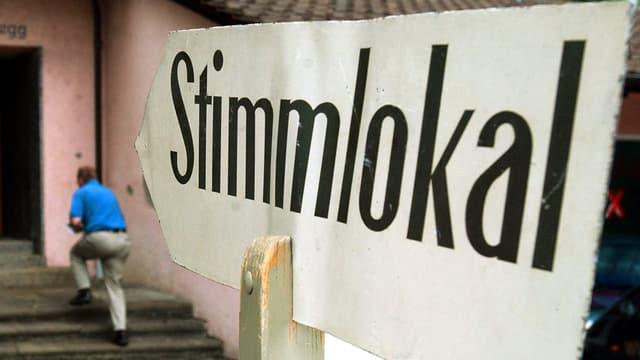 Eine Tafel mit der Aufschrift «Stimmlokal» deutet auf ein rosafarbenes Haus.