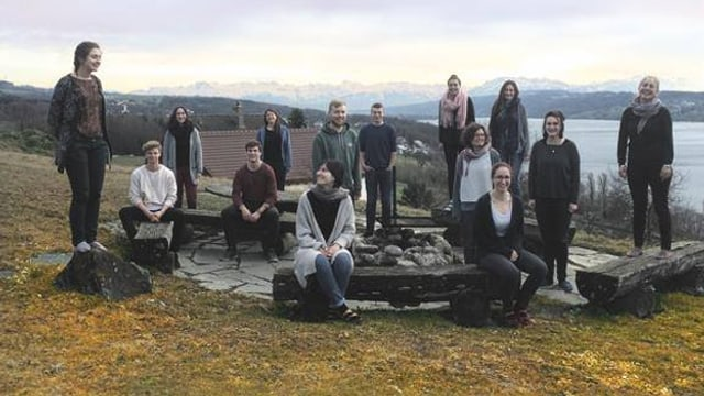 Junge Frauen und Männer stehen und sitzen im Freien, hinter ihnen liegt ein See.