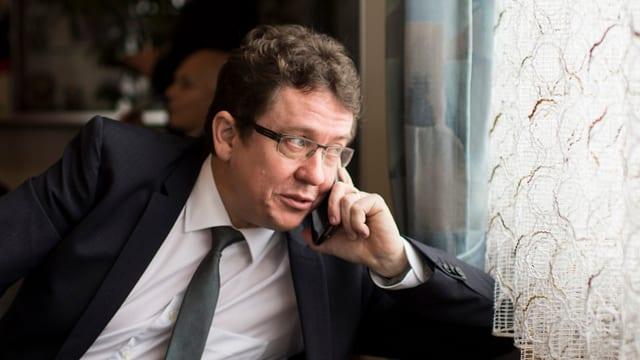 Ein Politiker im Anzug telefoniert am Fenster und blickt nach aussen